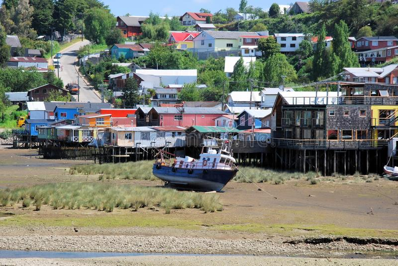 Chiloe Island, Chile, Stilt houses colored Castro during low tide. Palafitos colored stilt houses Castro during low tide with boat, Chiloe Island, Chile royalty free stock image