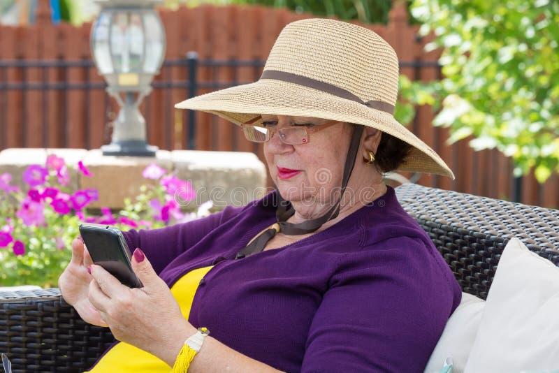 Stilvolle ältere Dame, die einen Smartphone verwendet lizenzfreies stockfoto