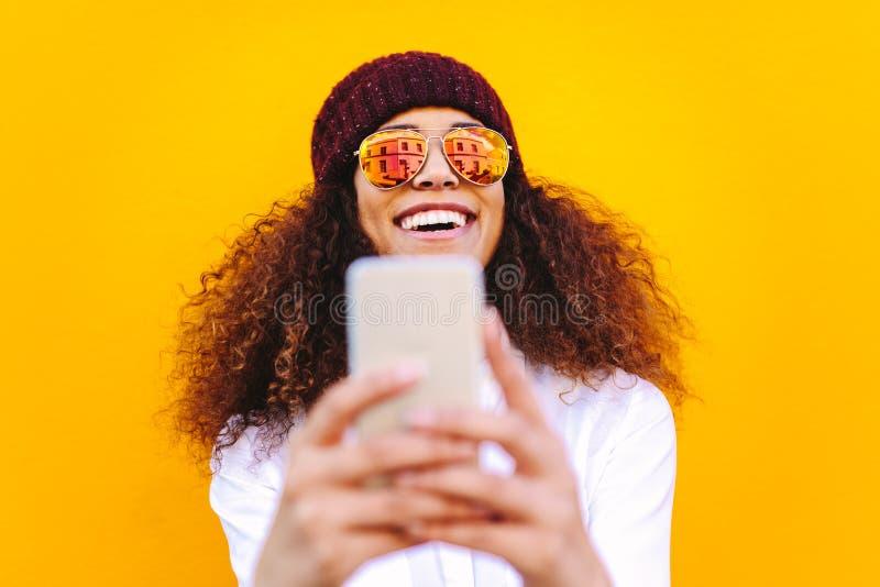 Stilvolle afrikanische Frau, die selfie macht lizenzfreie stockfotografie