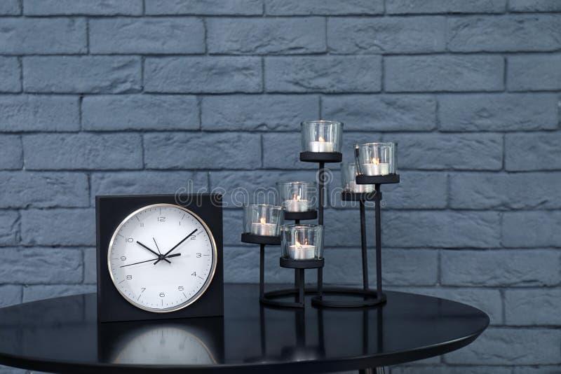 Stilvolle analoge Uhr und Kerzen auf Tabelle lizenzfreie stockfotografie