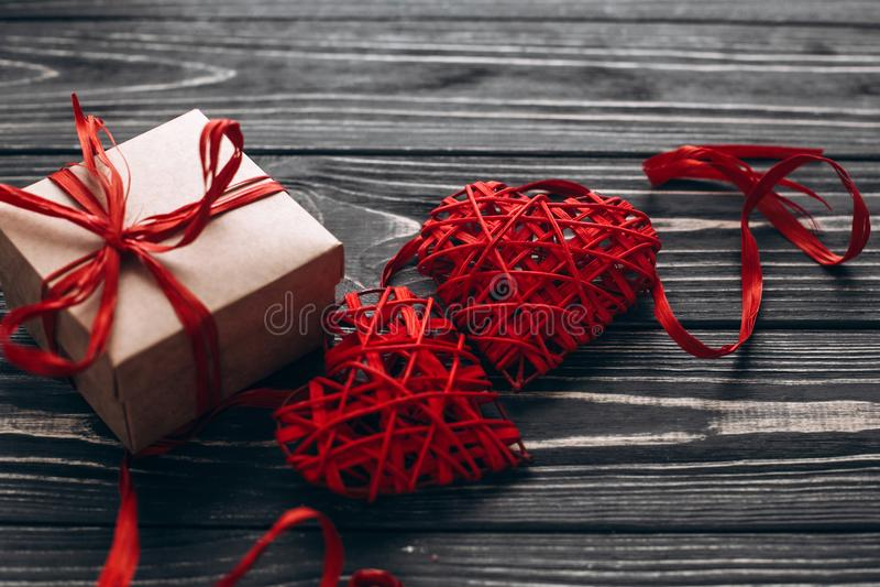 Stilvolle anwesende und zwei rote Herzen mit Band auf rustikalem Schwarzem w stockfoto