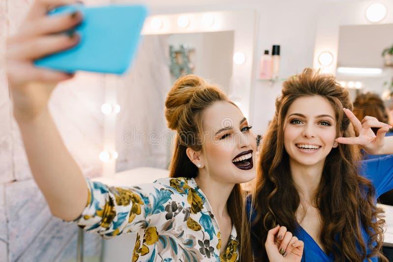 Stilvolle stilvolle attraktive Modelle des Portr?ts zwei mit stilvollen makeups, Luxusfrisuren, die selfie im Friseursalon machen stockfoto