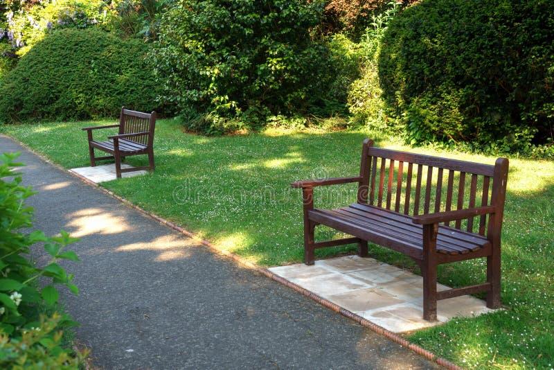 Stilvolle Bank im englischen Sommergartenpark stockfotos