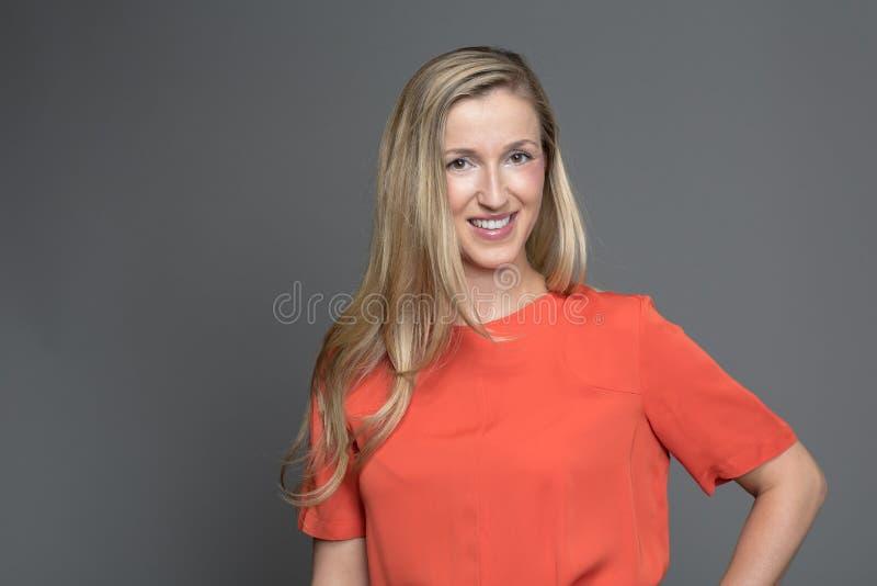 Stilvolle blonde Frau mit einem freundlichen Lächeln stockbild