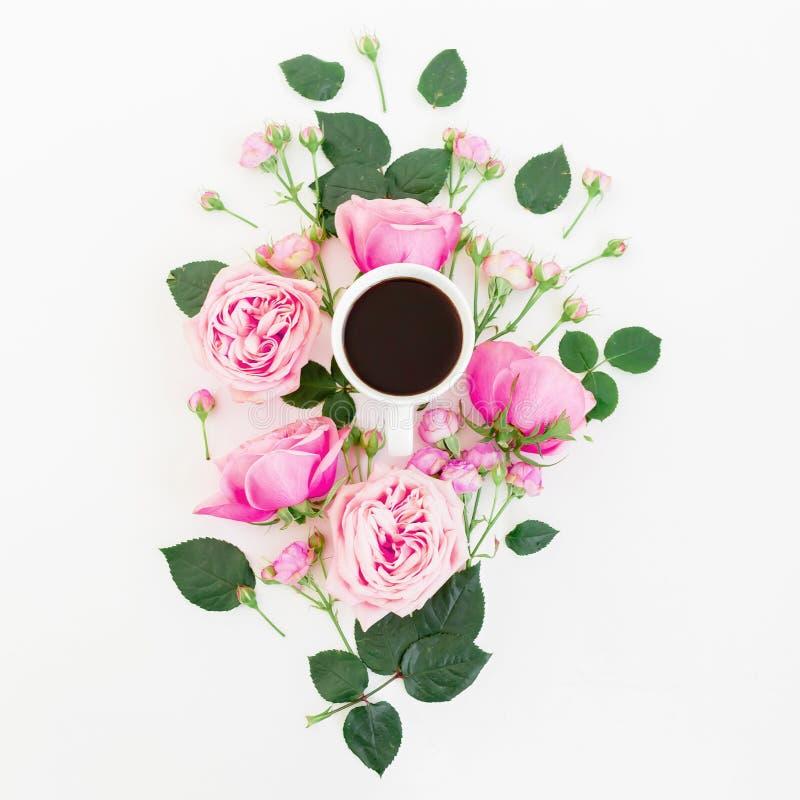 Stilvolle Blumenzusammensetzung gemacht von den rosa Rosen, von den Knospen und vom Becher schwarzem Kaffee auf weißem Hintergrun stockfotografie