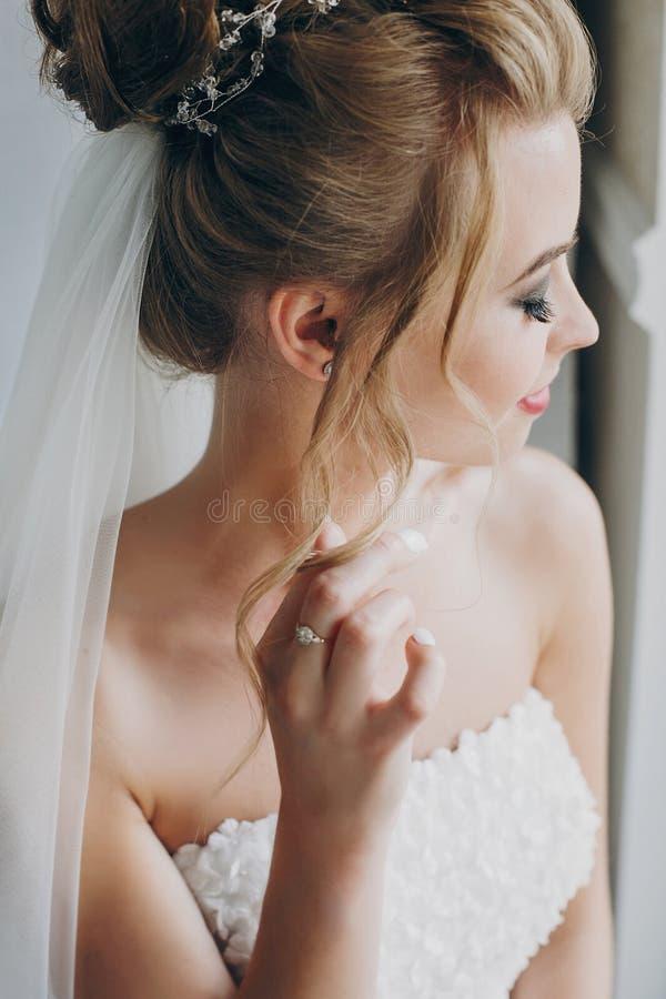 Stilvolle Braut, die im weichen Licht nahe Fensterbalkon im Hotelzimmer aufwirft Herrliches sinnliches Brautporträt Morgenvorbere stockfotos