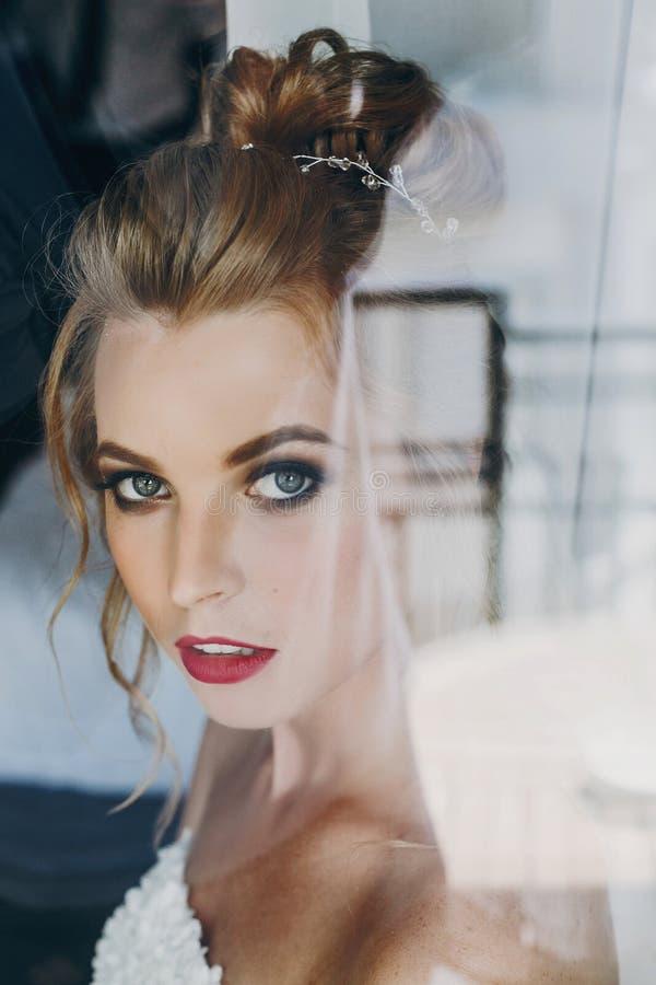 Stilvolle Braut mit dem überraschenden Make-up, das im weichen Licht nahe Fenster im Hotelzimmer aufwirft Herrliches sinnliches B lizenzfreies stockfoto