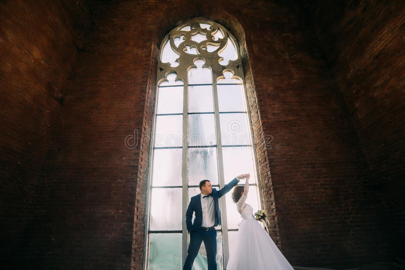 Stilvolle Braut und hübsches elegantes Bräutigamtanzen auf dem Hintergrund des Luxusinnenraums mit großem Fenster lizenzfreie stockfotografie