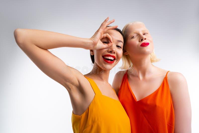 Stilvolle d?nne Frauen mit den hellen roten Lippen, die zusammen aufwerfen lizenzfreie stockfotografie