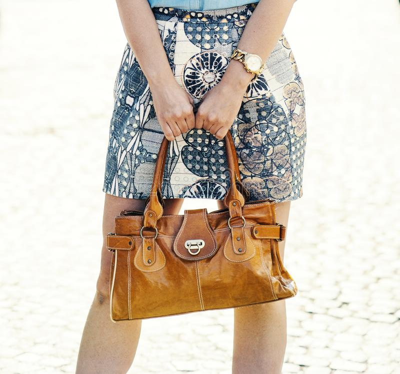 Stilvolle Dame, die natürliche LuxusLederhandtasche in den Händen hält lizenzfreie stockbilder
