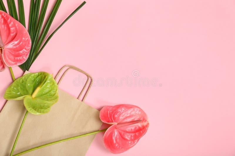 Stilvolle Ebene legen Zusammensetzung mit Einkaufstasche, tropischem Blatt und Blumen lizenzfreie stockfotos