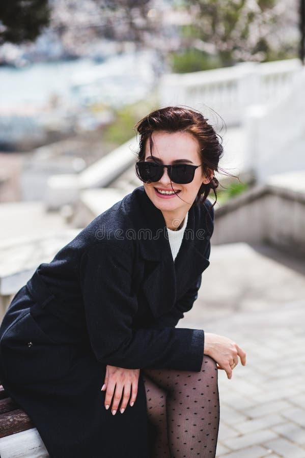 Stilvolle elegante glückliche Frau, die auf der Bank sitzt Sie kleidete im dunklen Mantel und in der Sonnenbrille an lizenzfreies stockbild
