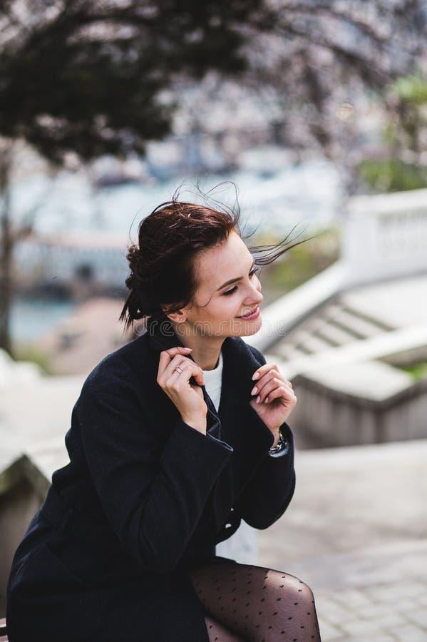 Stilvolle elegante glückliche Frau, die auf der Bank sitzt Sie kleidete im dunklen Mantel und in der Sonnenbrille an stockfotos