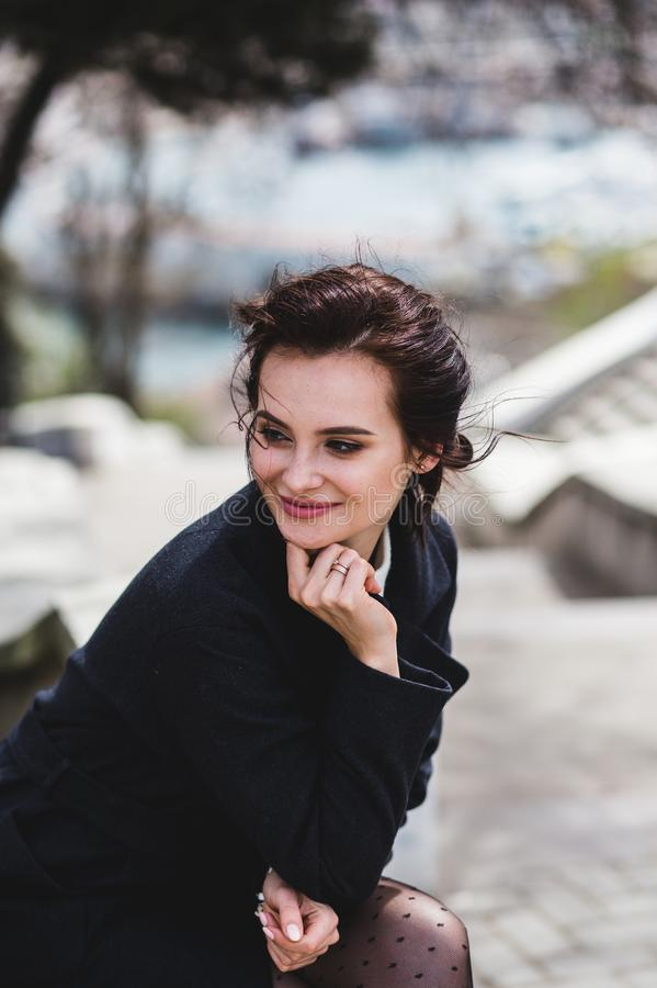 Stilvolle elegante glückliche Frau, die auf der Bank sitzt Sie kleidete im dunklen Mantel und in der Sonnenbrille an stockbilder