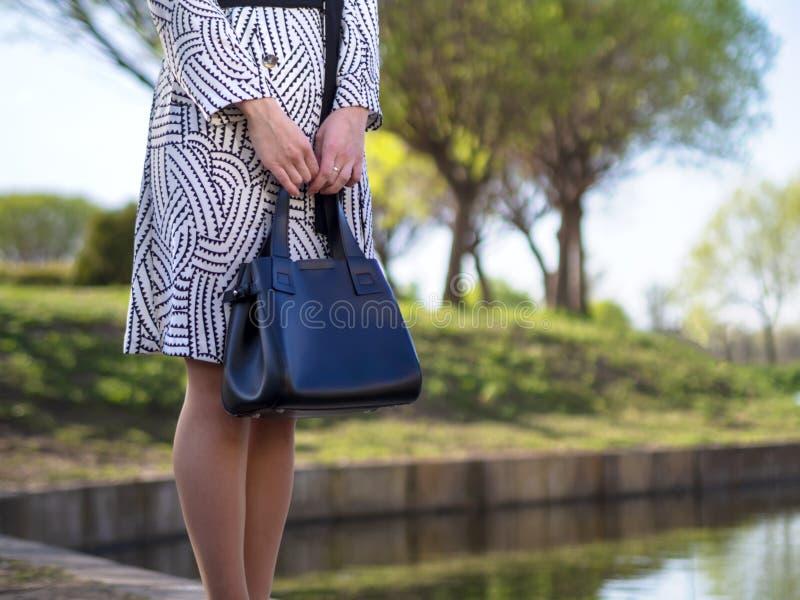 Stilvolle europäische junge Frau in einem Regenmantel, Strumpfhosen, Schuhe mit Fersen, mit einer schwarzen Ledertasche in ihren  lizenzfreies stockbild