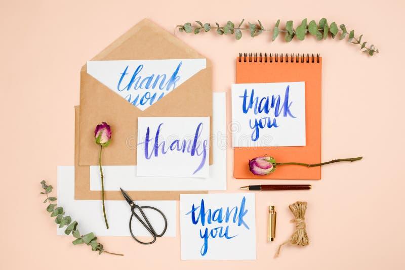 Stilvolle flatlay mit Weinleseumschlägen und handgemachten Karten mit dem Handlettering danken Ihnen, getrockneten Rosen, Scheren lizenzfreie stockbilder