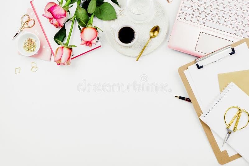 Stilvolle flatlay Rahmenanordnung mit rosa Laptop, Rosen, Gläsern und anderen Zusätzen auf Weiß stockfotos