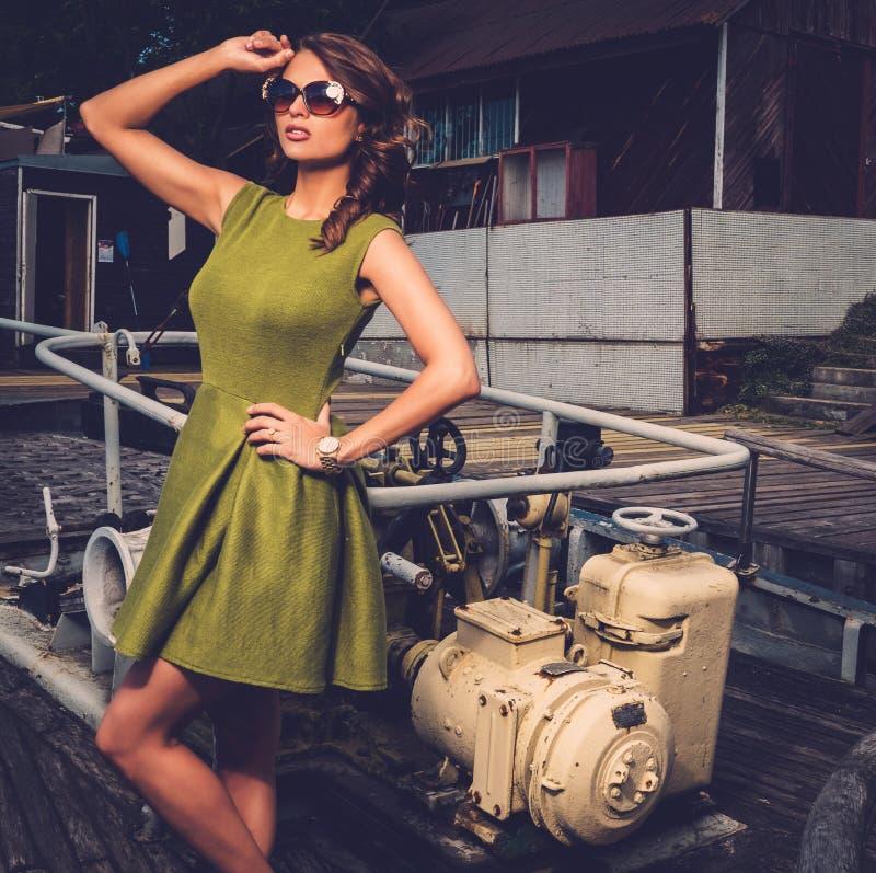 Stilvolle Frau auf altem rostigem Boot lizenzfreies stockbild