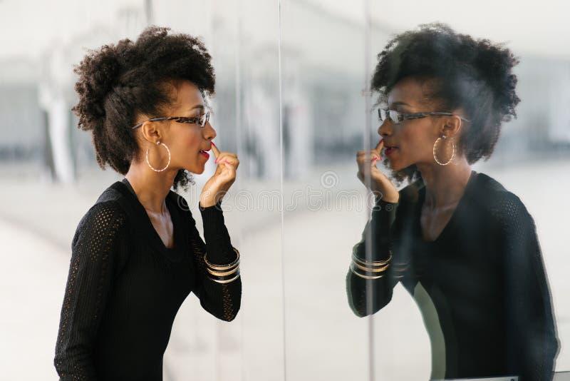 Stilvolle Frau der Afrofrisur, die ihr Make-up überarbeitet stockfoto