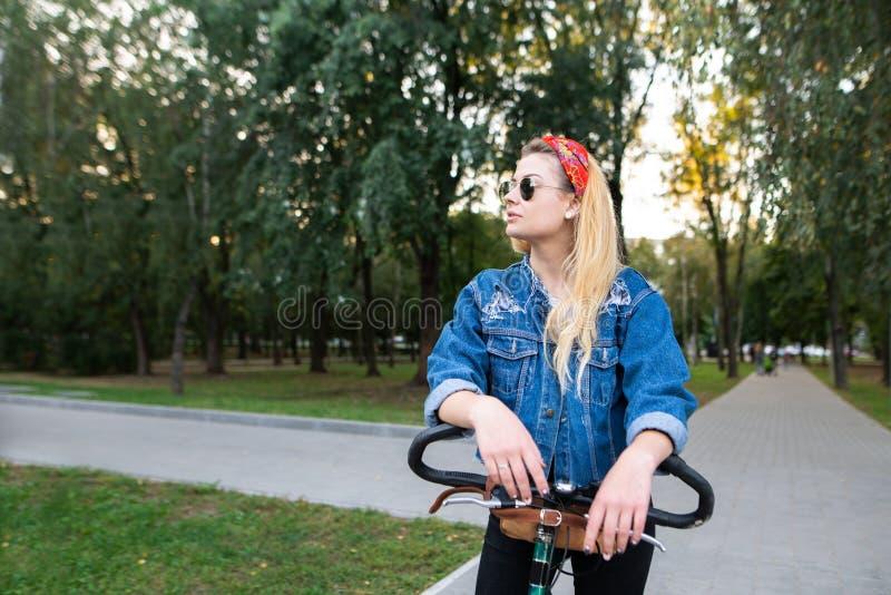 Stilvolle Frau in der Sonnenbrille und in einer Denimjacke steht mit einem Fahrrad im Park und schaut heraus zur Seite stockfotografie