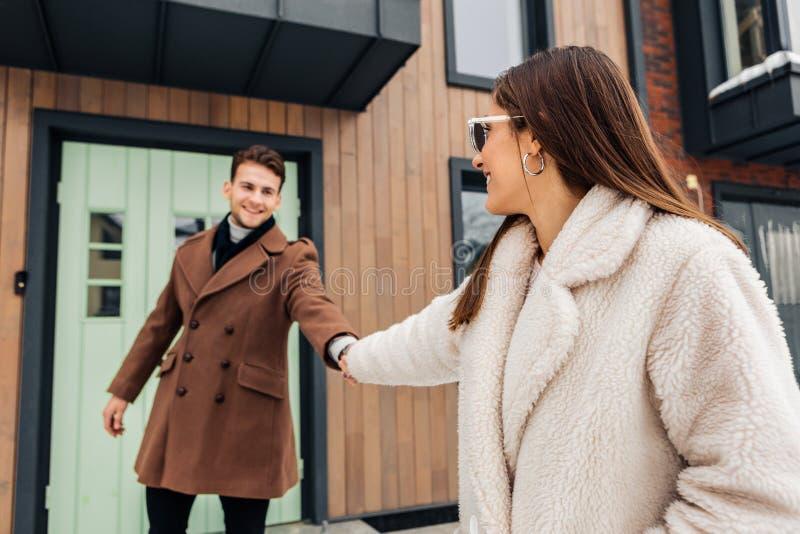 Stilvolle Frau, die den warmen beige Mantel bittet ihren Mann, spazierenzugehen trägt lizenzfreies stockfoto