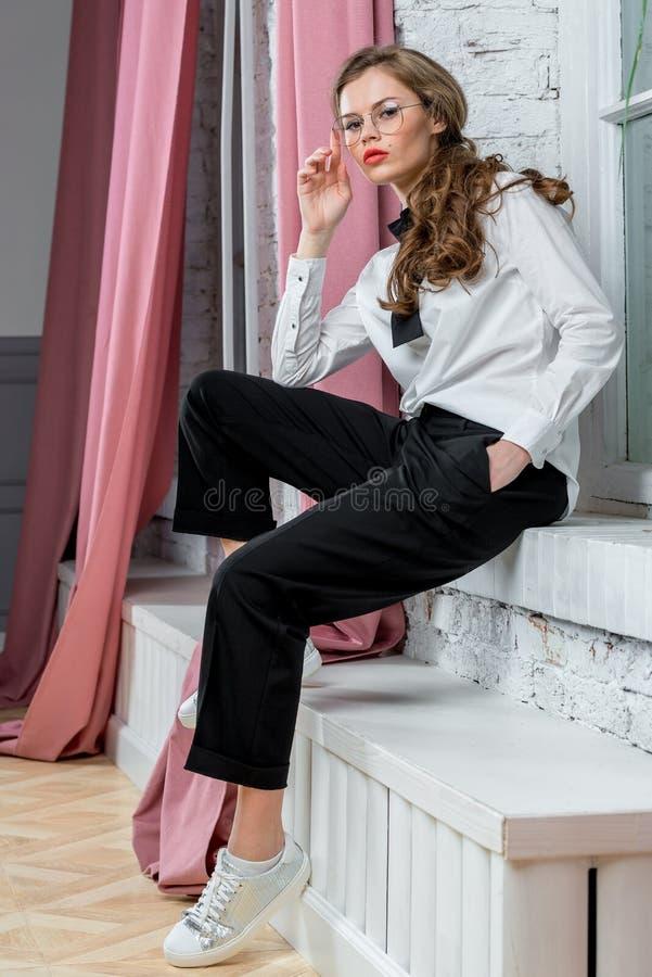 Stilvolle Frau, die in der Geschäftskleidung aufwirft stockfotos