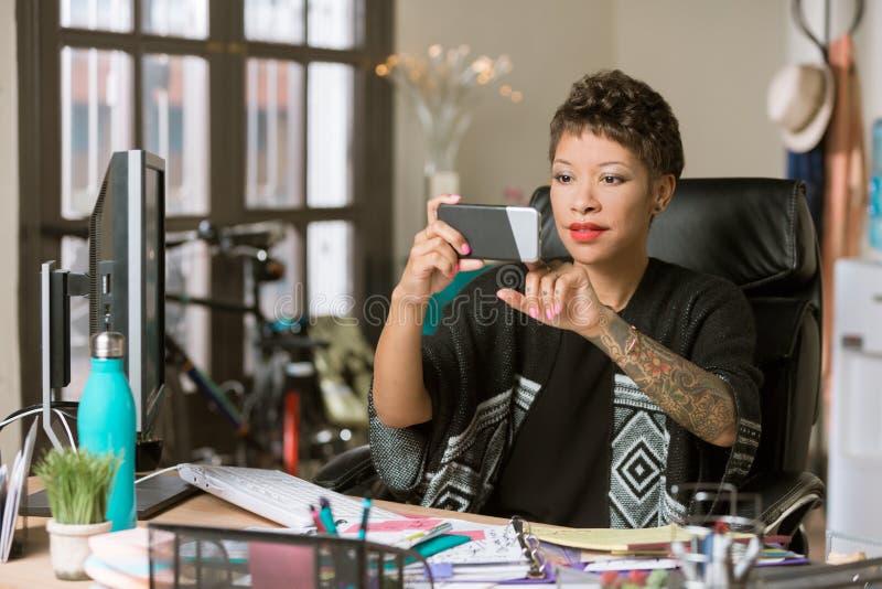 Stilvolle Frau, die ein Telefon in ihrem B?ro klaut stockfotos