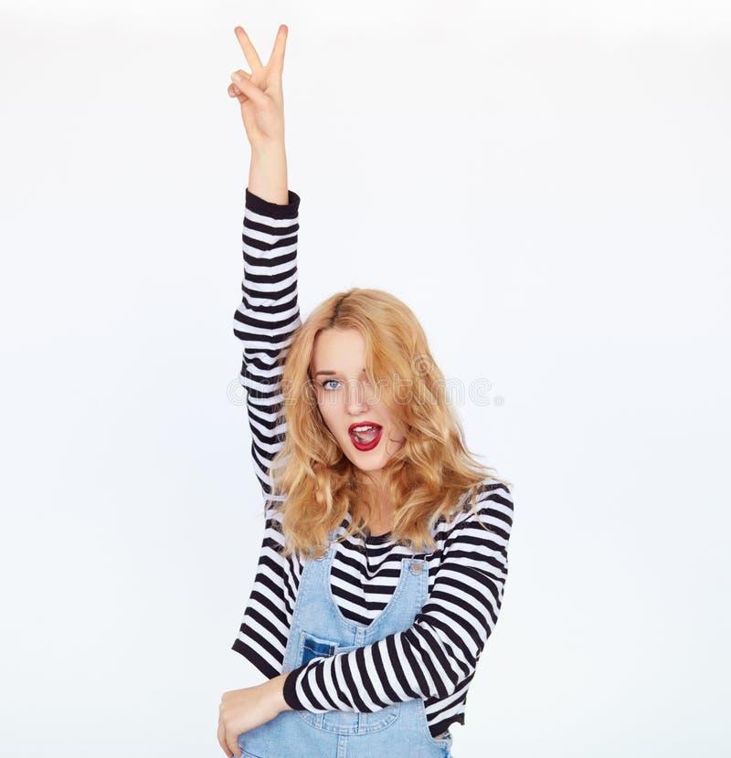 Stilvolle Frau, die Friedenszeichen mit den Fingern über weißem Hintergrund zeigt lizenzfreies stockfoto
