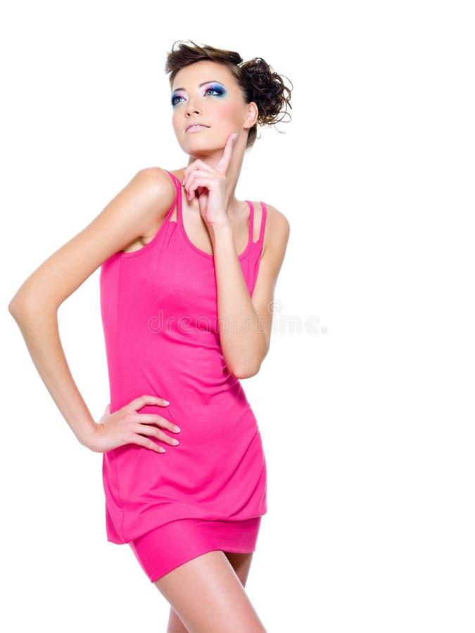 Stilvolle Frau, die im rosafarbenen Kleid aufwirft lizenzfreie stockfotografie