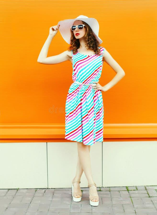 Stilvolle Frau im bunten gestreiften Kleid, Sommerstrohhut, der auf orange Wand aufwirft stockbilder