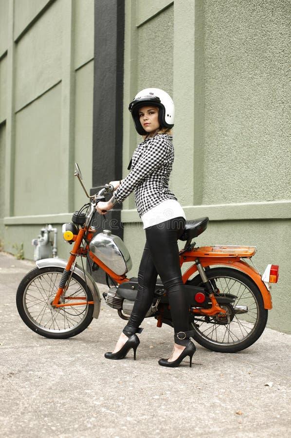 Stilvolle Frau mit Moped lizenzfreie stockfotos