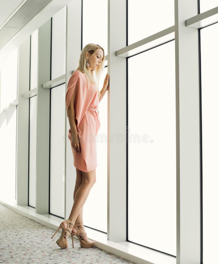 stilvolle Frau nahe dem Fenster im Bürogebäude lizenzfreie stockfotos