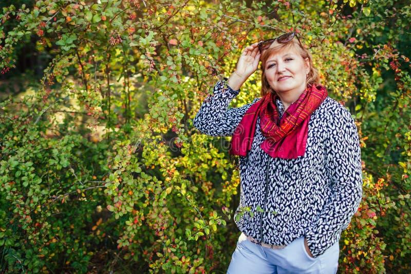 Stilvolle Frau von mittlerem Alter, die in tragender Fallkleidung und -Zubehör Herbstwaldälterer Dame aufwirft lizenzfreie stockfotos