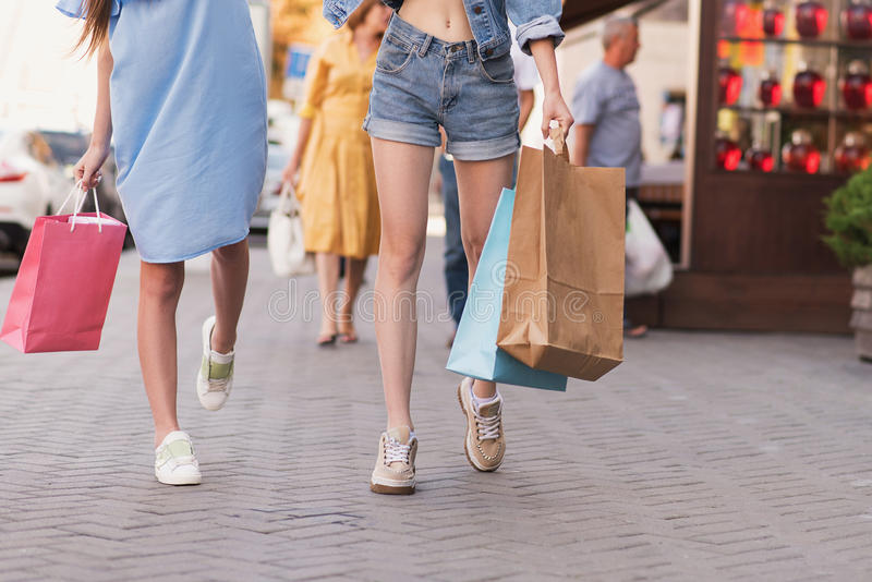 Stilvolle Frauen, die auf die Straße mit Käufen gehen stockfotos