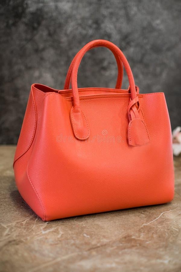 Stilvolle Frauen ` s Handtasche auf einem Steinhintergrund Orange, helle Koralle Kleidung und Zubehör Elegante Ausstattung lizenzfreie stockbilder