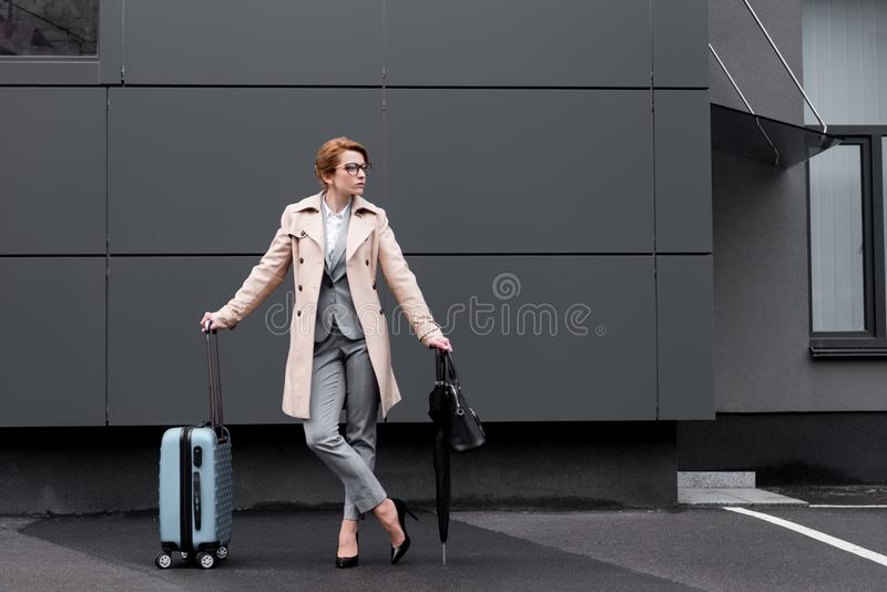 stilvolle Geschäftsfrau im Mantel mit Kofferwartetaxi stockfoto