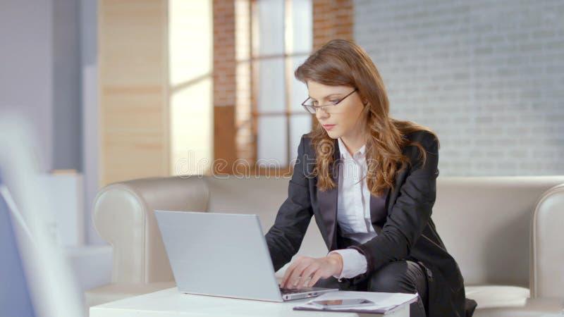 Stilvolle Geschäftsfrau oder Rechtsanwalt, die an Laptop im Firmenbüro, Technologie arbeiten lizenzfreie stockfotos