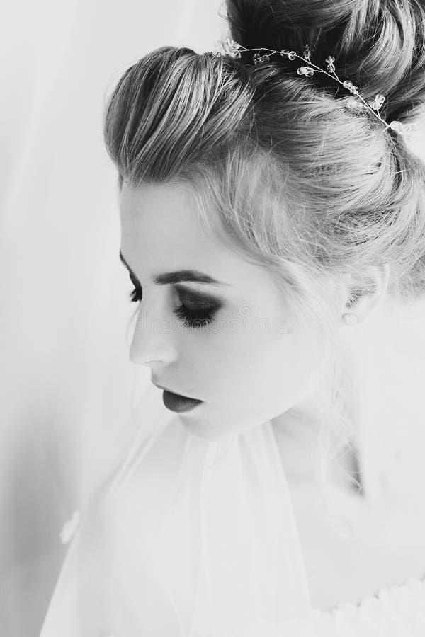 Stilvolle glückliche Braut mit dem überraschenden Make-up, das im weichen Licht nahe Fenster im Hotelzimmer aufwirft Herrliches s lizenzfreie stockfotos