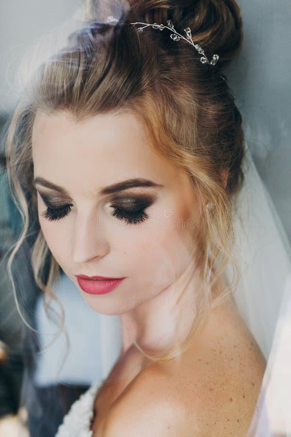 Stilvolle glückliche Braut mit dem überraschenden Make-up, das im weichen Licht nahe Fenster im Hotelzimmer aufwirft Herrliches s stockbilder