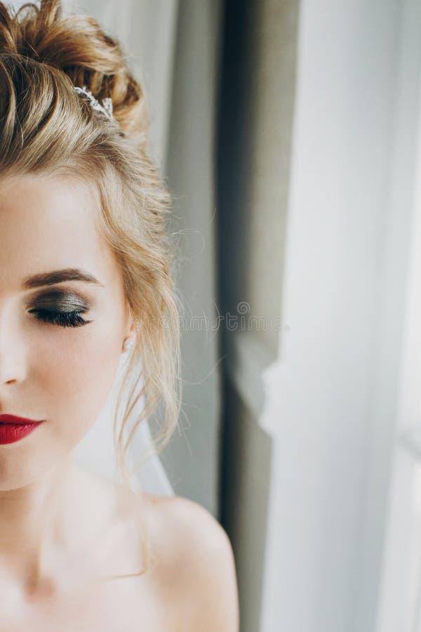 Stilvolle glückliche Braut mit dem überraschenden Make-up, das im weichen Licht nahe Fenster im Hotelzimmer aufwirft Herrliches s stockfoto