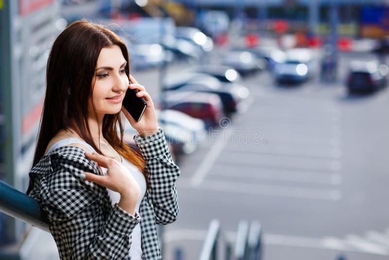 Stilvolle glückliche Frau der Junge recht, die am intelligenten Telefon im c spricht stockfotos