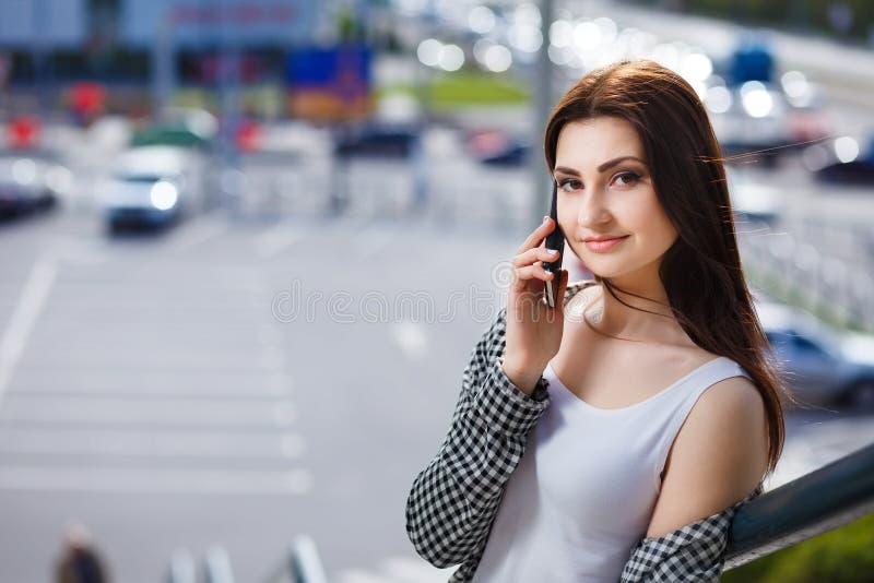 Stilvolle glückliche Frau der Junge recht, die am intelligenten Telefon im c spricht lizenzfreie stockbilder