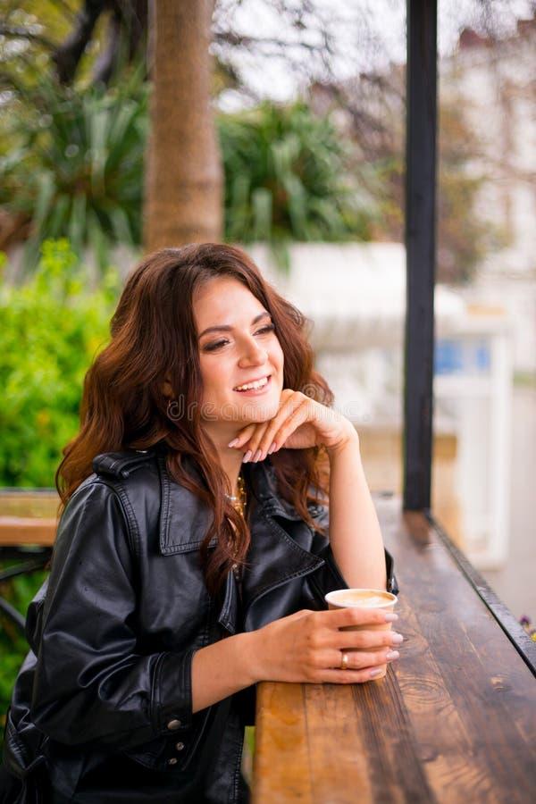 Stilvolle glückliche junge Frau im Straßencafé Sie h?lt Kaffee zum Mitnehmen lizenzfreie stockfotos