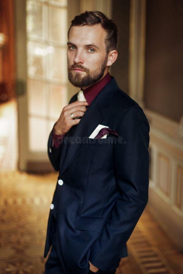 Stilvolle hübsche Bräutigamaufstellung, sicher schauend, wenn SU überrascht wird stockfotografie