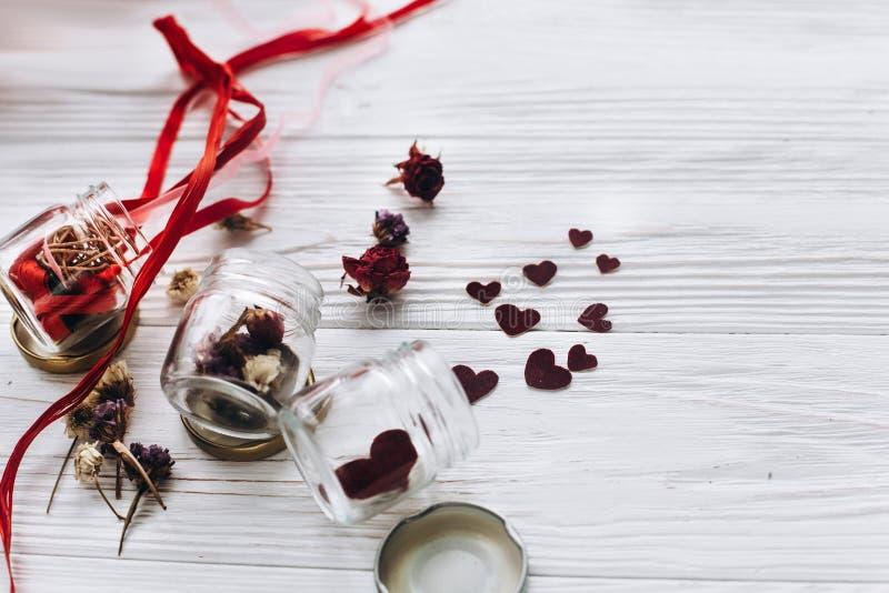 Stilvolle Herzen im Glasgefäß und in den Rosen und Bänder auf weißem woode lizenzfreie stockbilder