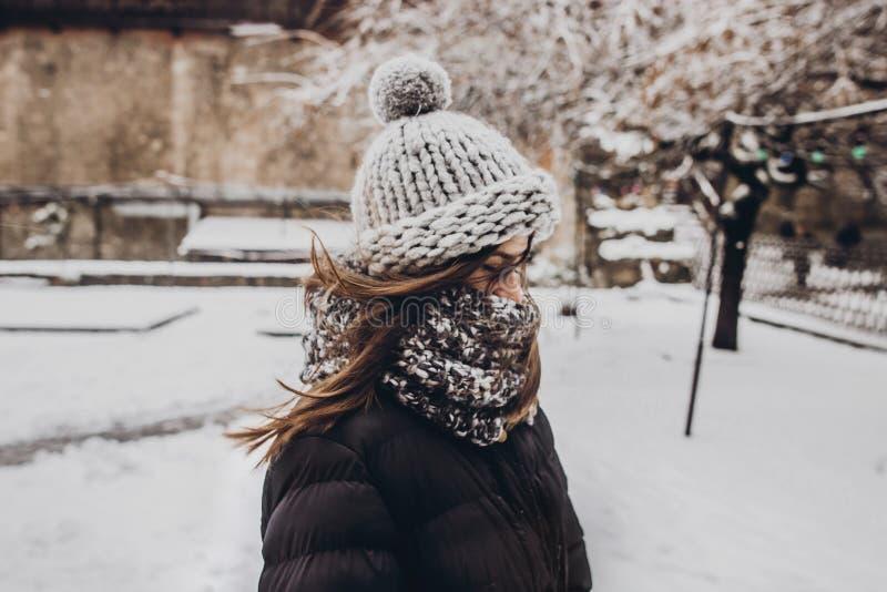 Stilvolle Hippie-Frau in der Strickmütze, die in schneebedecktem Stadt stre steht lizenzfreie stockfotos