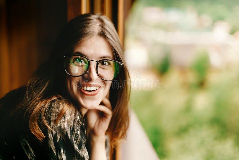 Stilvolle Hippie-Frau, die am Fenster mit unterhaltenem Lächeln in wo sitzt lizenzfreie stockfotos