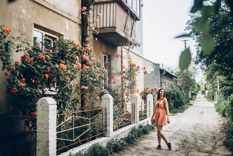 Stilvolle Hippie-Frau, die an schönen rosa und roten Rosen O steht lizenzfreies stockfoto