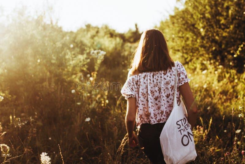 Stilvolle Hippie-Frau mit eco Tasche im Sonnenlicht gehend unter Willen stockfoto