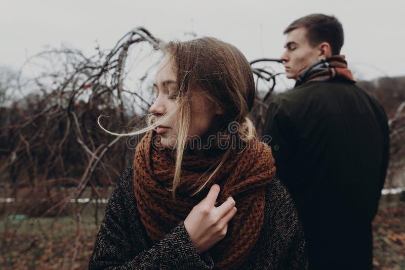 Stilvolle Hippie-Frau und -mann, die im windigen Herbst aufwirft, parken sensu lizenzfreies stockfoto